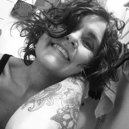 Svartvit bild på leende silversmed HannaCharlotta med tatuering på underarm