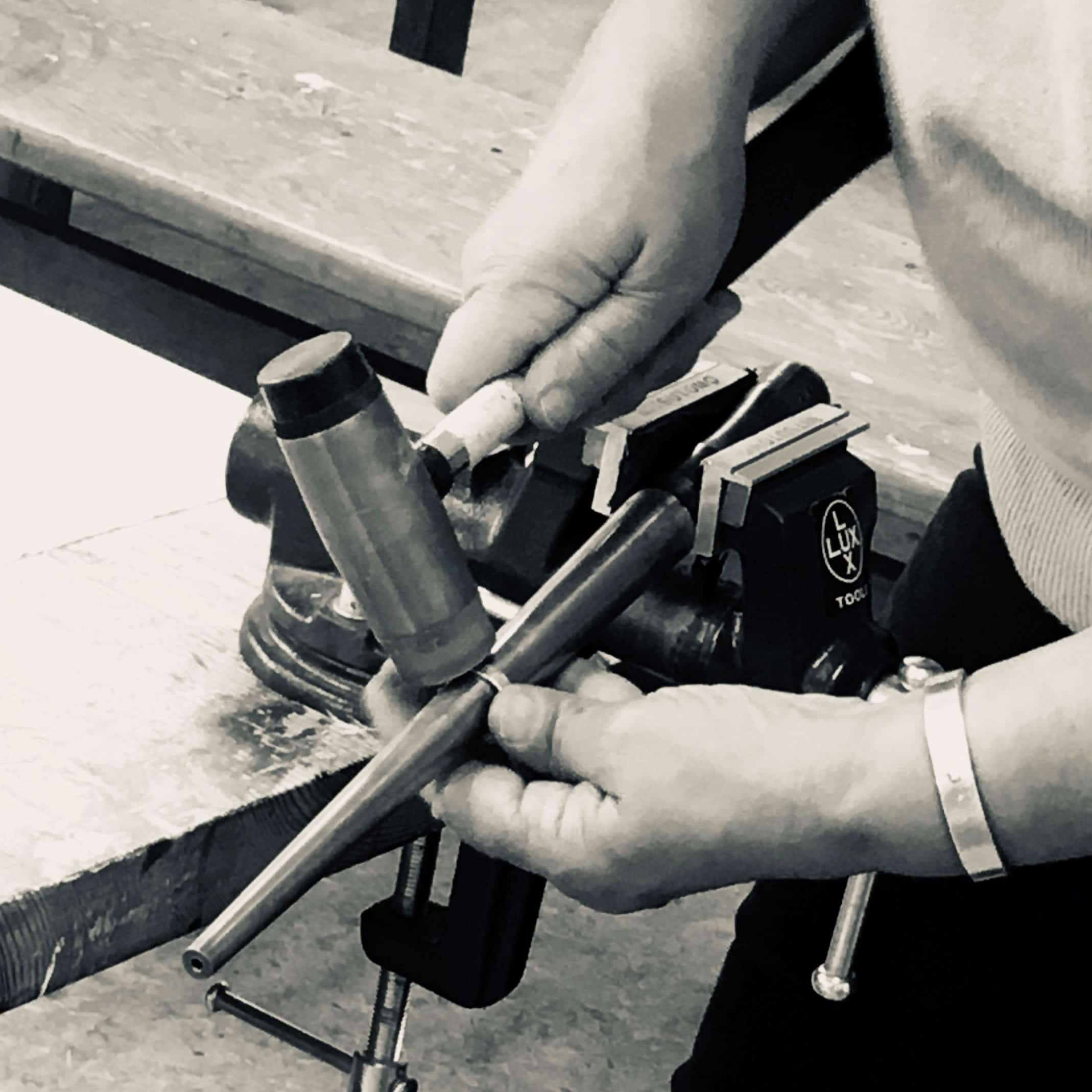Deltagare under workshop i silversmide hamrar ring i silver på en ringregel